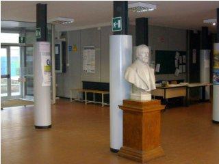 Fotografia dell'atrio senza persone: pavimento marrone, da cui spicca il busto in marmo grigio di Mazzini, vicino a colonne portanti dell'Istituto