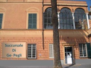 L'ingresso della succursale di Genova Pegli, ospitata da Villa Doria Centurione. Facciata rosa pesca con ingresso e finestre del piano terreno. Il primo piano ha grandi vetrate. Si vede inoltre un tronco di palma